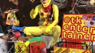 Chicken outfit man playing drums