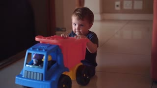 A small child plays with a big truck