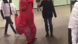 Red trex dinosaur walking through subway station
