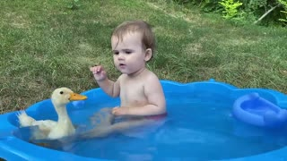Cute baby and duck taking bath together