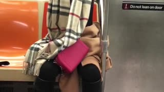Woman raising arms up and down on subway train