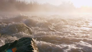 Foaming river water flows down large black rocks