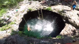 Two women jumping into a water hole.