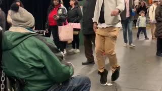 Guy dances to man playing harmonica in subway station