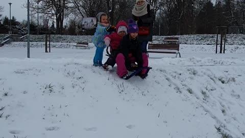 Kids eat snow after crashing on sled