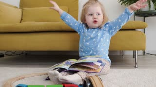 A little girl with A Book flopping her hands