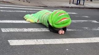 Person crawling on street floor green caterpillar