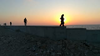 French Tourists Walks Along Side In Sunset Orange View