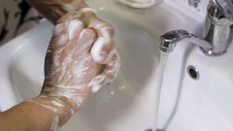 Person washing their hands in the bathroom