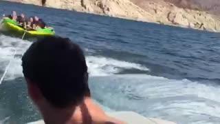 Girls on green tube on water girl falls