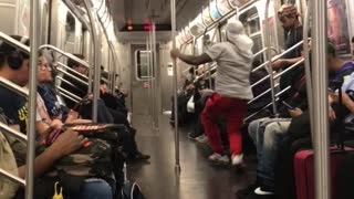 Man in red pants dances on subway train