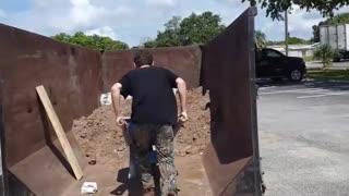 Guy blue wheelbarrow dirt falls in trash can