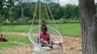 Little boy enjoys hammock swing with his puppy