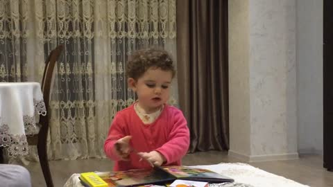 Baby girl adorably reads favorite fairy tale to parents