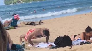 Man in red swim shorts push ups on beach