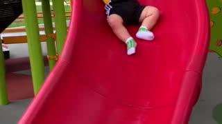 Baby Slips Slowly Down Slide