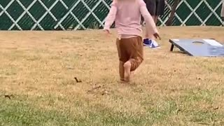 Little Girls Spins and Falls Down in Grass