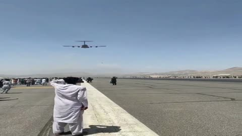 People seen holding on to a plane as it prepares to take off from Kabul Airport