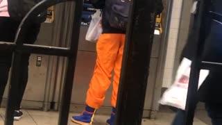 Guy wears orange ninja pants at subway station ticket booth