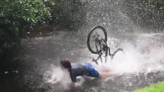 Slow motion guy riding bike into lake