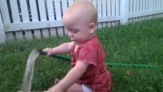 Baby discovers garden hose