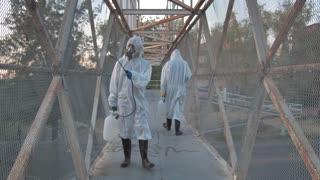 people with masks sanitizing-a-pedestrian-bridge