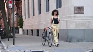 A Woman Walking With Her Bicycle