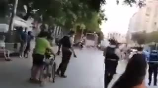Police attempt to arrest a woman without mask, everyone removes mask to help her.