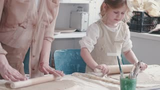A Mother And Daughter Flattening Dough With Rolling Pins
