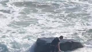 Surfer Struggles Against Pounding Waves