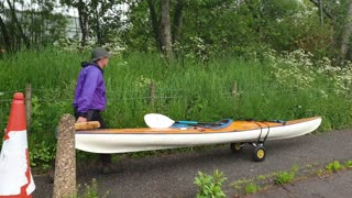 Pushing a sea kayak through the centre of a town in Scotland