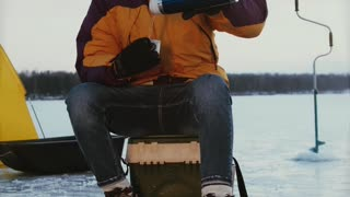 A Man Drinking Coffee While Ice Fishing
