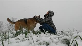 A Woman Playing With Her Dog Outside In A Snowy Days