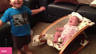 A child tries to playfully feed his baby brother