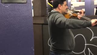 Guy plays violin together with another guy playing cello across subway station