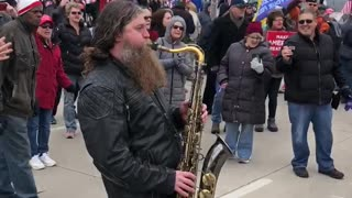 Saxophonist Plays National anthem in street during Milwaukee protest