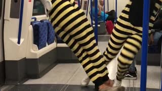 Couple yellow bee costume subway blue pole spin