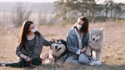 Two girls with two Husky dogs