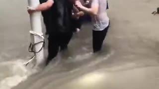 Central China floods- woman being pulled out and save