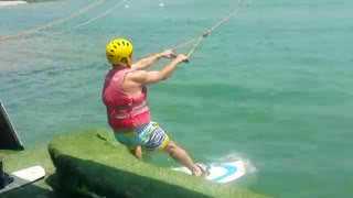 Man wakeboards and gets pulled by boat, flies of board and into the water