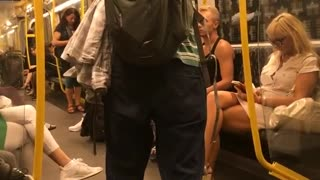 Man in green striped shirt playing flute on subway