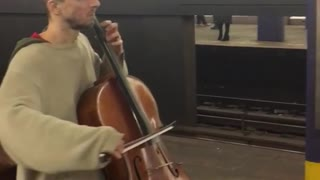 Man plays cello inside subway station, guys playing violin across station
