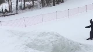 Guy snowboards off ramp and falls before jumping, mom laughs loudly