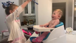 Baby girl ecstatic while being fed by big sister