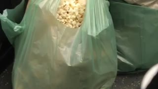Woman eating popcorn from green bag