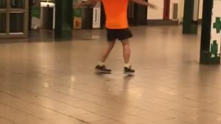Guy orange shirt bald spinning in subway train station