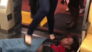 Guy laying on subway floor people walking over him