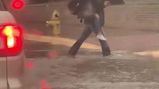 Boy Carries Fellow Students Across Flooded Street