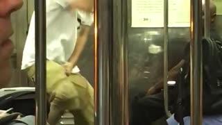 Guy black headphones white shirt khaki shorts dancing subway