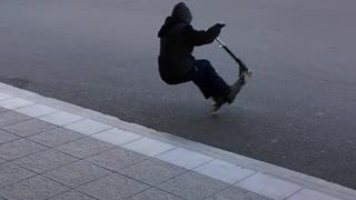 Kid black sweater jump scooter fall back